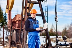 Portrait of petrolium engineer, wearing blue overalls and orange helmet, with a laptop, standing with his back to an oil rig, checking oil pumping unit, making notes in his computer