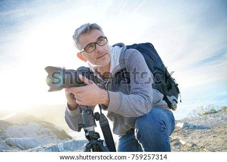 Portrait of photographer taking pictures in natural landscape