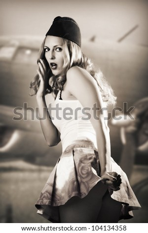 Portrait of pin up girl about vintage aircraft in retro style - stock photo