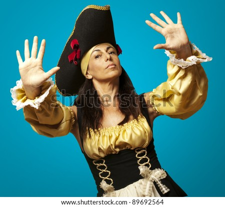 portrait of pirate woman gesturing stop against a blue background
