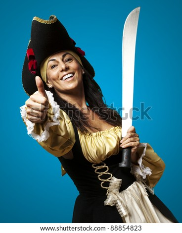 portrait of pirate woman holding a sword and gesturing ok against a blue background