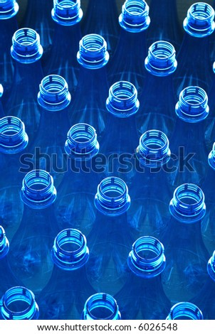 Portrait of plastic water bottles in factory viewed from top down - stock photo