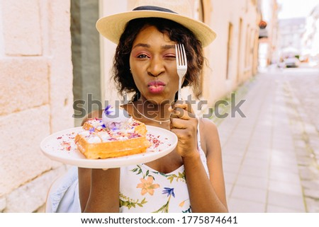Portrait of playful african woman in straw hat hiding eye with fork, holding a plate of belgian waffles sitting outdoor cafe, surrounded with lavender flowers and healthy vegan food. European city.