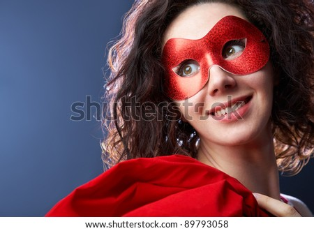 Portrait of playful beautiful young woman wearing red carnival mask