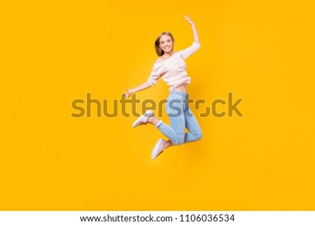 Portrait of playful crazy girl jumping in the air looking at camera enjoying weekend having perfect mood isolated on yellow background