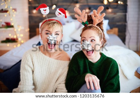 Portrait of playful friends at Christmas  #1203135676