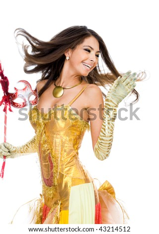 Portrait of playful woman in glamorous attire and mask in hand