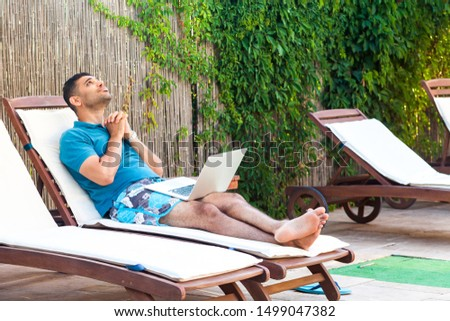 Portrait of pleading handsome bearded young adult prayer man in blue t-shirt and shorts lying on cozy sunbed with laptop on poolside and pleased to help him god. Lifestyle, outdoor, summer vacation