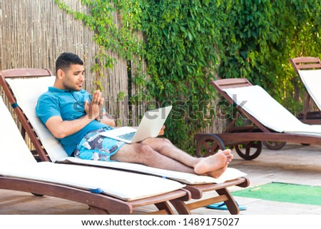 Portrait of pleading handsome bearded young adult worker man in blue t-shirt and shorts lying on cozy daybed with laptop on poolside and pleased to help him through webcamera online. Lifestyle,outdoor