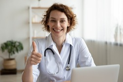 Portrait of pleasant happy young female therapist physician looking at camera, showing thumbs up gesture, recommending online medical service or advertising regular checkup meeting in hospital.