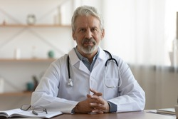 Portrait of pleasant professional older mature gp physician in white coat sitting at table, waiting for patient. Smiling trusted middle aged male doctor looking at camera, medical insurance service.