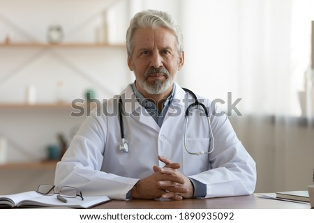 Portrait of pleasant professional older mature gp physician in white coat sitting at table, waiting for patient. Smiling trusted middle aged male doctor looking at camera, medical insurance service. Stock photo ©