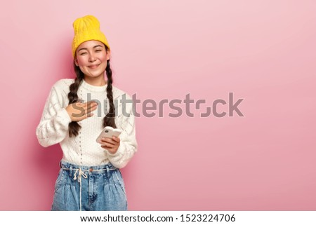 Portrait of pleased Korean woman keeps palm on chest, being touched by heartwarming words, holds modern electronic device, receives good message, wears yellow hat, casual white jumper and jeans