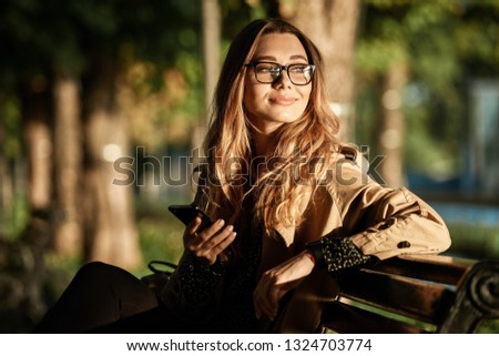 Portrait of pleased woman 20s wearing coat and eyeglasses using smartphone while sitting on bench in sunlit alley