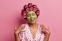 Portrait of pleased young African American woman stands with closed eyes, smiles gently, imagines something nice, applies green face mask, hair curlers, stands indoor, pink background. Domestic style