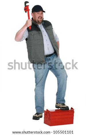 portrait of plumber holding adjustable spanner with foot resting on toolcase