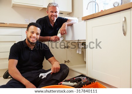 Portrait of plumber with apprentice in domestic kitchen