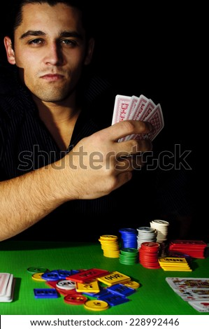 Portrait of Poker player with poker face and cards on a dark background. Good luck in card games on the big money
