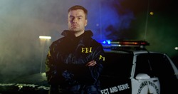 Portrait of police officers with serious faces looking at camera. FBI agent work at the scene at night, police car with lights on background.
