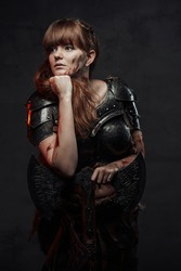 Portrait of posing in dark background female viking with huge axe and grimy face dressed in dark armour.