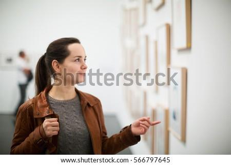 Portrait of positive adult brunette girl in art museum #566797645