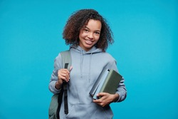 Portrait of positive African-American student girl in hoodie holding stack of books against blue background
