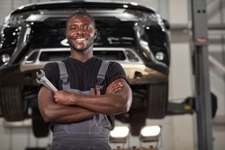portrait of positive afro american auto mechanic in uniform posing after work, he is keen on repairing cars, automobiles.