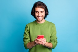 Portrait of positive bearded person texting write post nice sweater isolated on blue color background