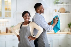 Portrait of positive black woman and her husband wiping dishes at kitchen