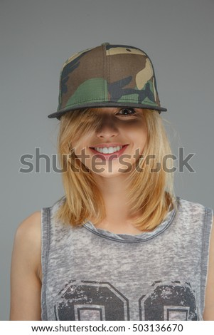 b5f62f4a0b8e17 Portrait of positive blonde girl in military cap isolated on grey background.  #503136670