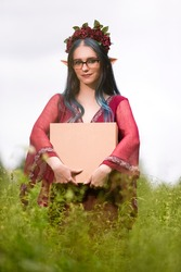 Portrait of Positive Caucasian Girl Posing in Flowery Garland and Artistic Ears Offering Gift Box on Green Field. Vertical Image Composition