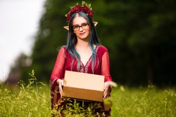 Portrait of Positive Caucasian Girl Posing in Flowery Garland and Artistic Ears Offering Gift Box on Green Field. Horizontal Shot