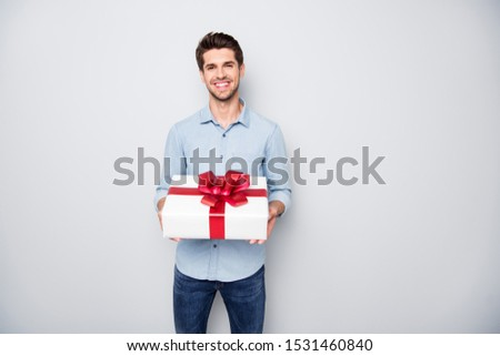 Portrait of positive charming lover man hold gift box present for 14-february 8-march feel content enjoy holiday wear style denim jeans clothing isolated over grey color background