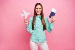 Portrait of positive cheerful girl have tourism work tour hold tickets white paper card plane enjoy traveling air voyage abroad wear turquoise clothes isolated over pastel color background