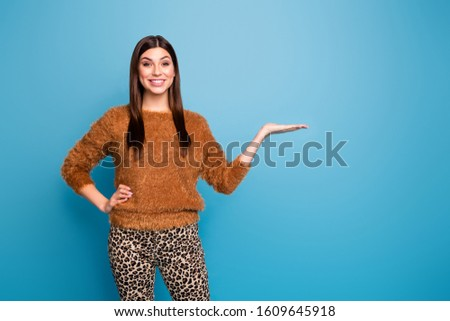 Portrait of positive cheerful girl hold hand demonstrate promo adverts recommend wear spring winter good look clothes isolated over blue color background