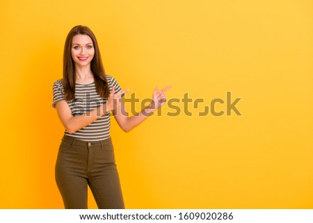 Portrait of positive cheerful girl promoter point index finger copyspace recommend follow promo adverts pick tips wear good looking clothes isolated over bright color background