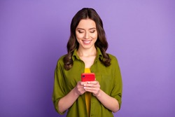 Portrait of positive cheerful girl use cellphone read social network information search comment feedback wear good look outfit isolated over purple color background