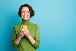 Portrait of positive cheerful girl use smart phone look copyspace share social media news wear style stylish trendy jumper isolated over blue color background