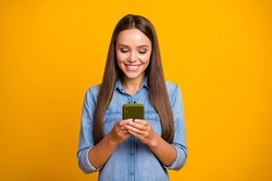 Portrait of positive cheerful girl use smartphone read social network novelties enjoy online communication wear good look clothes isolated over bright shine color background