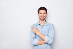 Portrait of positive cheerful guy promoter point index finger recommend ads select suggest adverts  wear casual style clothes isolated over grey color background