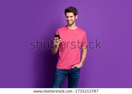 Portrait of positive cheerful guy use cell phone enjoy chatting repost share social network information wear style stylish trendy outfit isolated over bright shine color background