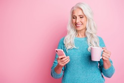 Portrait of positive cheerful modern old woman granny use smartphone follow social media post comment hold hot latte beverage mug wear blue jumper isolated over pink color background