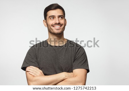 Portrait of positive Europen man pictured isolated on gray background