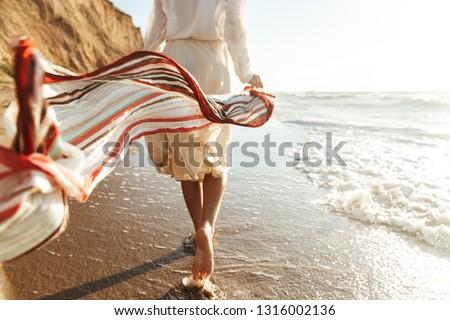 Portrait of positive girl 20s walking with waving scarf along seashore
