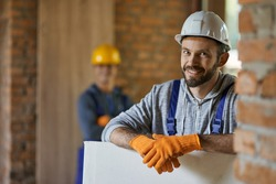 Portrait of positive, handsome young male builder in hard hat smiling at camera, holding drywall while working at construction site