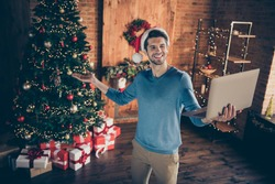 Portrait of positive happy guy in santa claus hat hold laptop video call invite his family to x-mas tradition noel celebration in house with newyear ornament lights