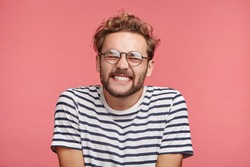 Portrait of positive hipster guy grins at camera, shows white teeth, closes eyes with pleasure, rejoice spending time with friends or girlfriend, feels carefree and relaxed. People and happiness