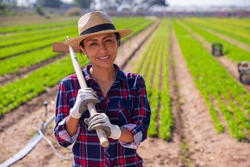 Portrait of positive latino woman with hoe on his field background