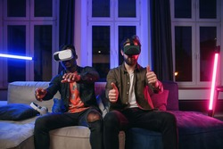 Portrait of positive likable satisifed multiracial male mates which sitting together on the couch in somebody's room and competing between each other in video game using special 3d goggles