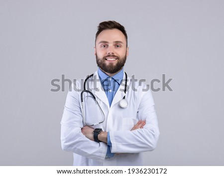 Portrait of positive male doctor posing with crossed arms and smiling at camera over grey studio background